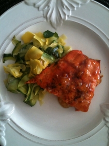 Orange lacquered salmon fillet and ribbons of yellow and zucchini squashes